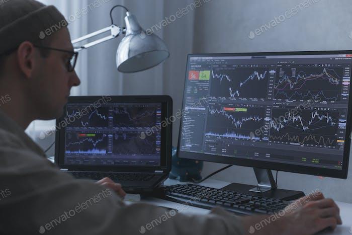 Nachdenkliche ernsthafte Trader Broker analysiert Börsengrafiken am PC und Laptop