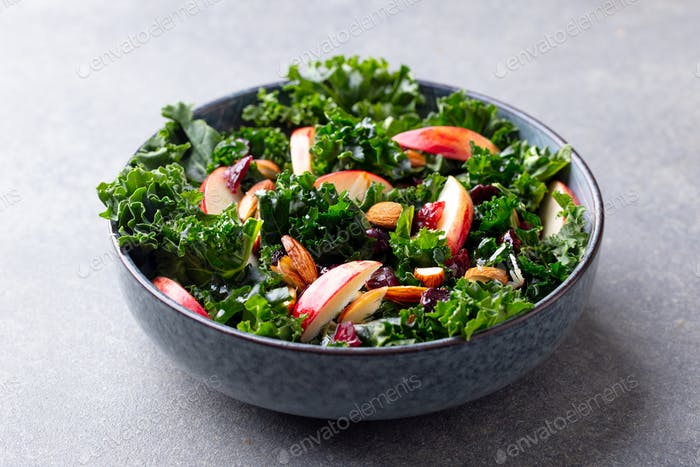 Kale Salad with Apples and Nuts. Grey Background. Close up.