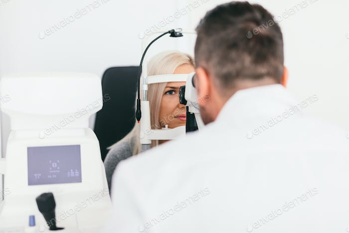 Doctor checking his patient's eyesight.