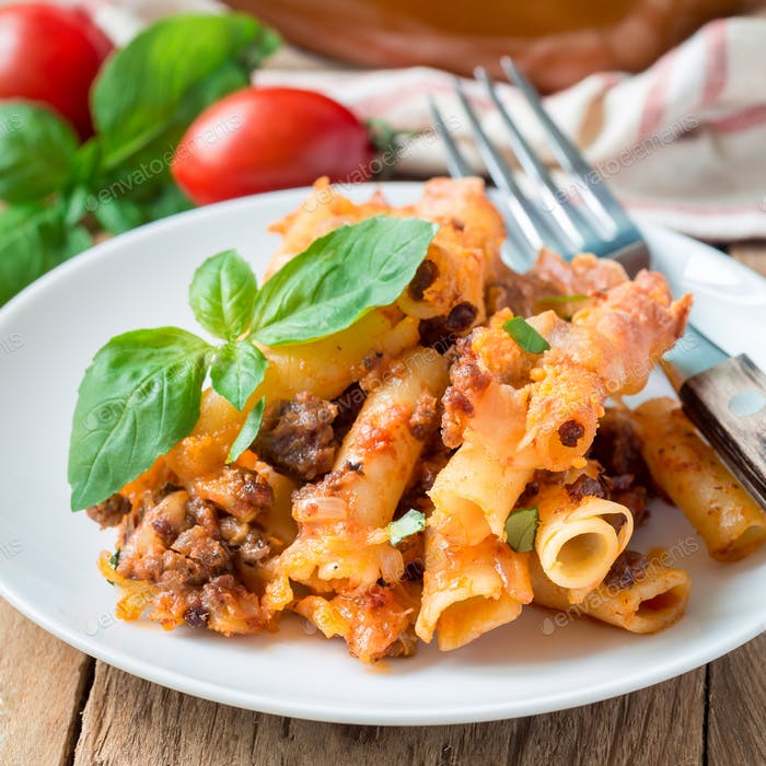 Ziti bolognese on a white plate, pasta casserole with minced meat, tomato sauce and cheese, square