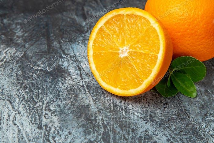 Halber Schuss ganz und halbiert frische Orangen auf grauem Hintergrund