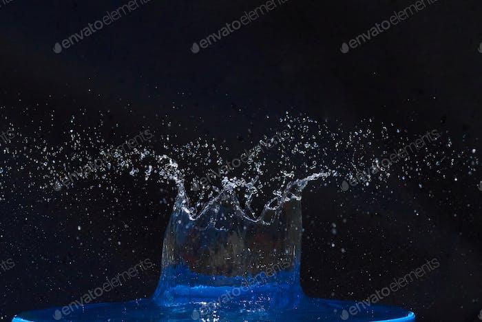 Splash of water crown on blue surface.