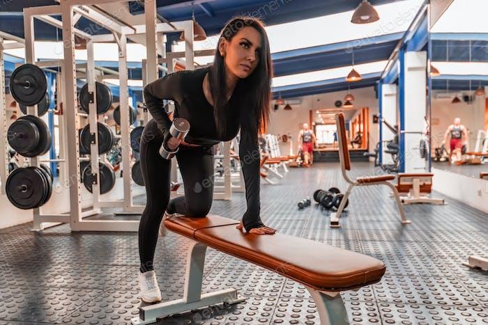 Junge schöne Frau trainiert Bizeps im modernen Fitnessstudio