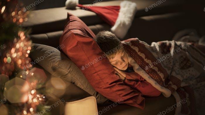 Cute boy waiting for Santa and sleeping on the sofa