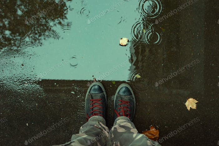 Standing in the drizzle puddle on the street
