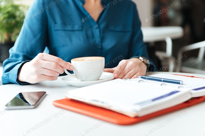 Cropped image of a woman sitting at the cafe table