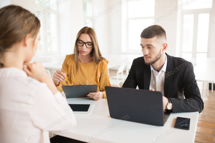 Pensive business man with laptop and business woman in eyeglasse