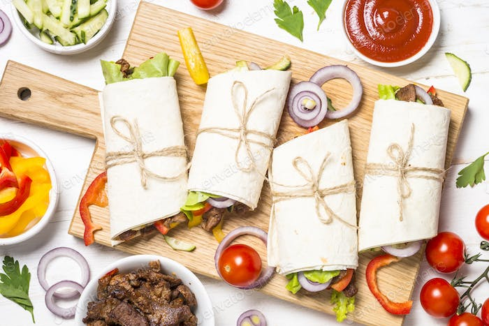 Burritos tortilla wraps with beef and vegetables on white backgr