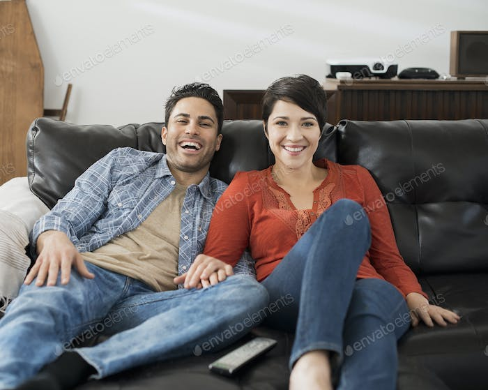 A man and woman sitting on a sofa, side by side, holding hands and watching a screen.