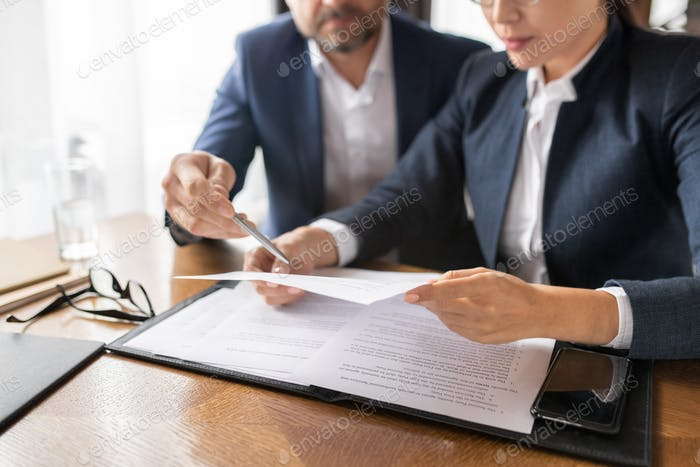 Contemporary businessman pointing at paper held and read by young Asian woman
