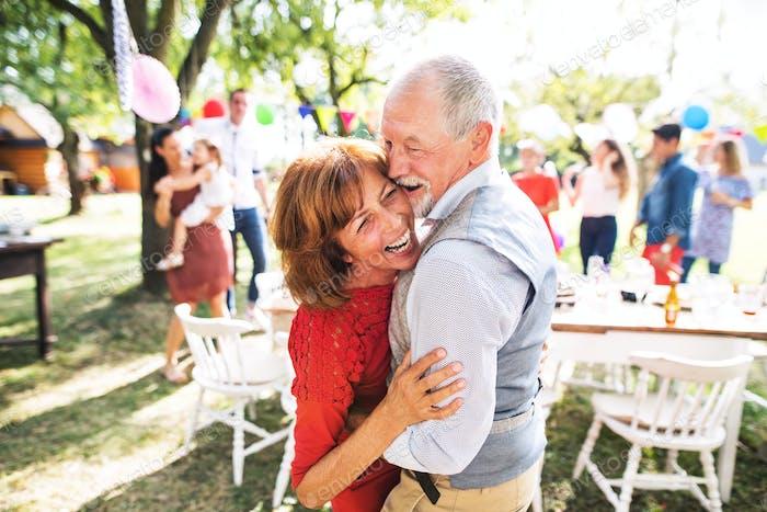 Ein älteres Paar tanzt auf einer Gartenparty draußen im Garten.