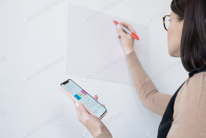 Young businesswoman or coach holding smartphone with flow chart