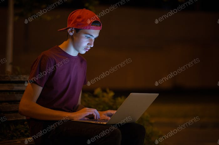 Teenage boy with a laptop in the park.
