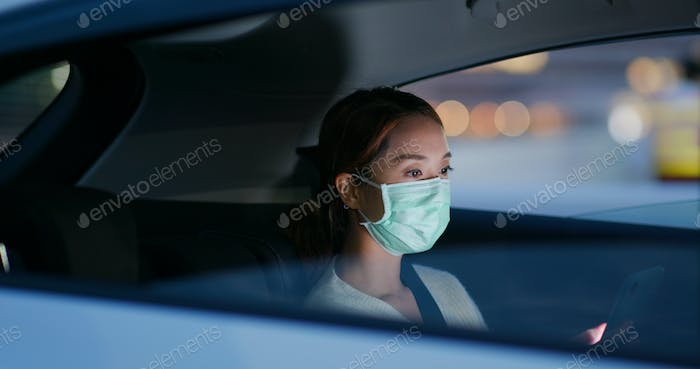 Woman wear medical mask and use of mobile phone sit inside the car