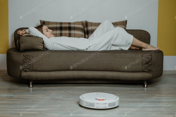 Robotic Vacuums, Robot Mops. Smart home. Robotic Vacuum Cleaner while Woman Relaxing on sofa
