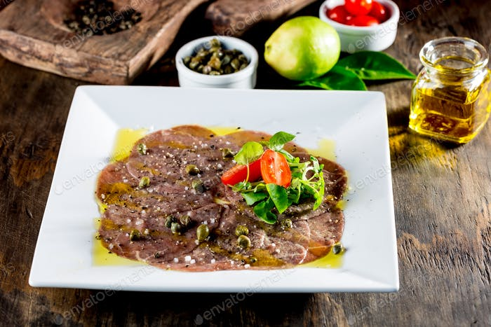 Beef carpaccio on white plate, wooden background. Close up.