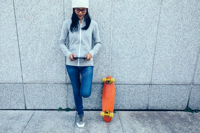 Woman skateboarder use mobile phone against wall in city