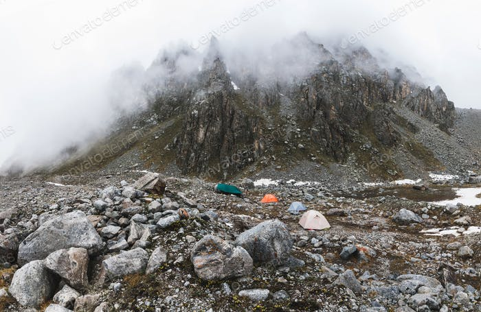 Сamping with tents high in the mountains in winter. Fog, snow and cold weather. Mountain range