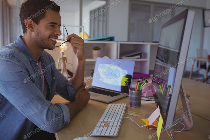 Smiling businessman looking at computer in office