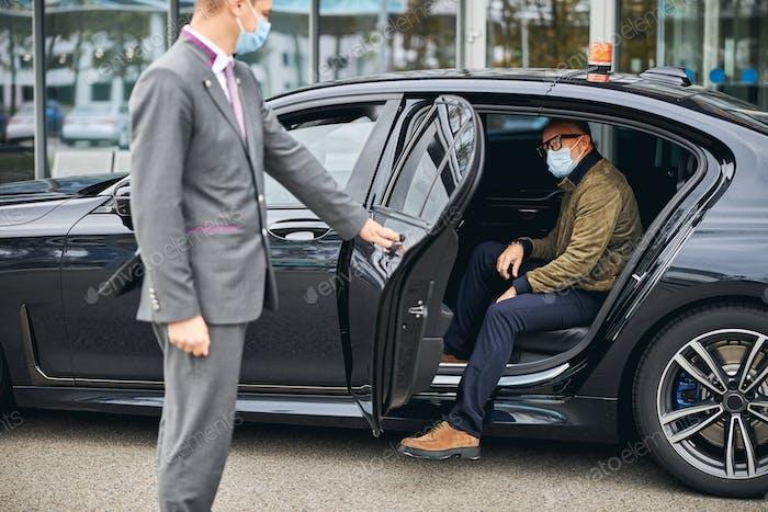 Mann mit Brille steigt aus dem Elite-Taxi
