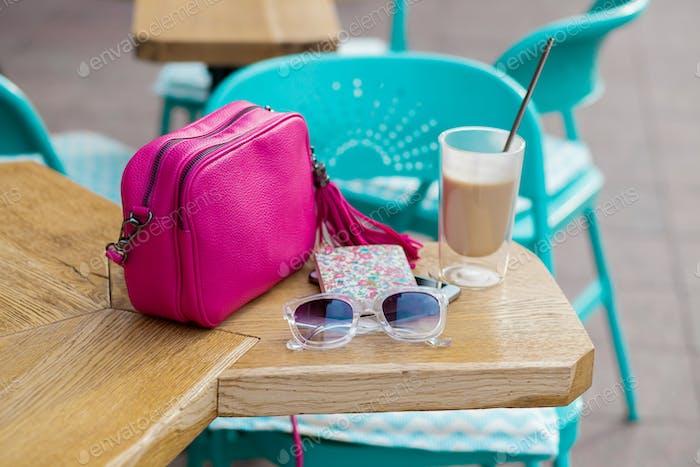 Objekte auf dem Tisch im Stadtcafé auf der Straße angeordnet, Frauenaccessoires