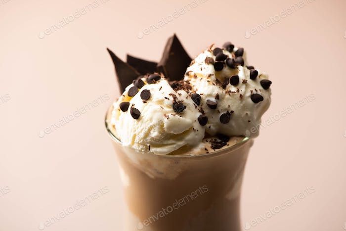 Glass of milkshake with ice cream, pieces of chocolate and candies on beige background