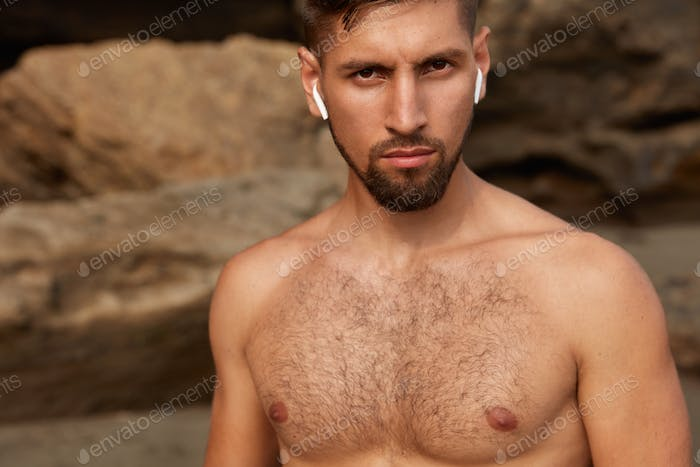 Cropped shot of young muscular build man witn naked body, serious expression and stubble, has active