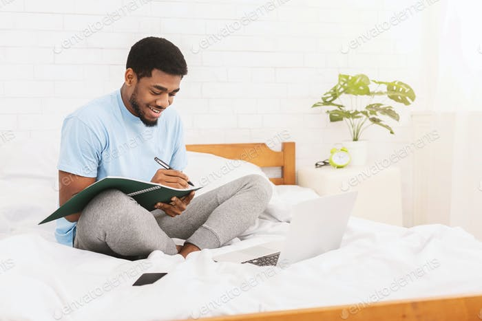 Cheerful black student learning online in bed
