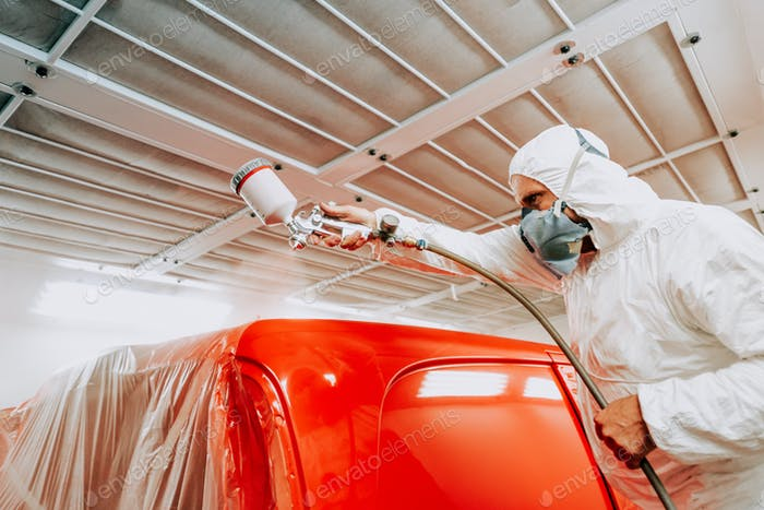 Automotive mechanical engineer painting the body of a red car with special suit