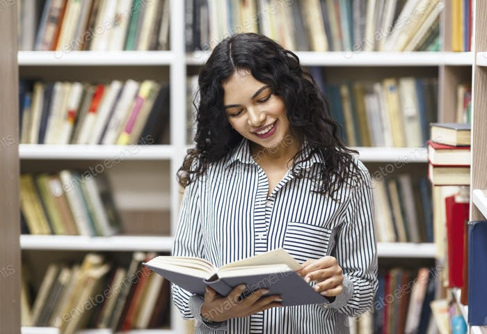 Smiling latina woman reading a book at library