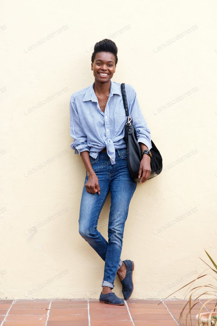 smiling black woman leaning against wall