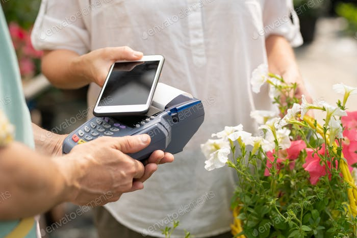 Young client of flower shop holding smartphone over payment machine