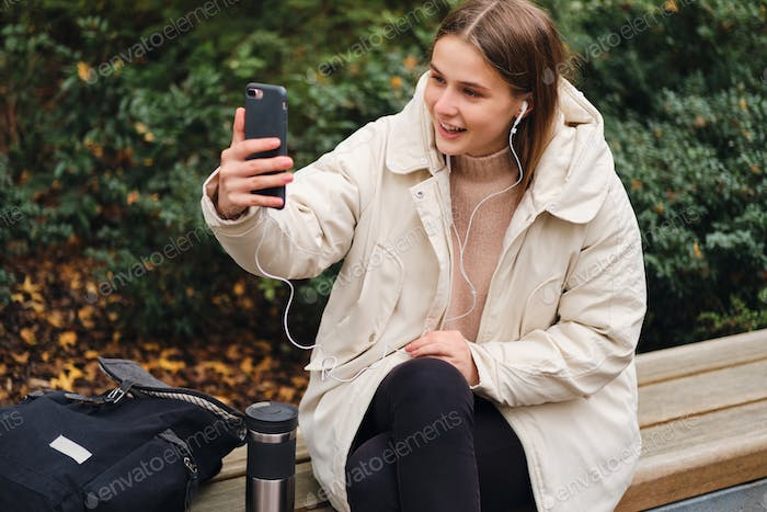 Attractive cheerful girl in down jacket happily talking on video chat on cellphone in city park