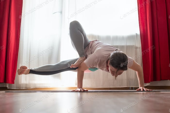 Young woman working out indoors, doing yoga exercise handstand asana