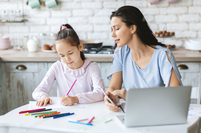Proud mother looking how her little daughter drawing in kitchen