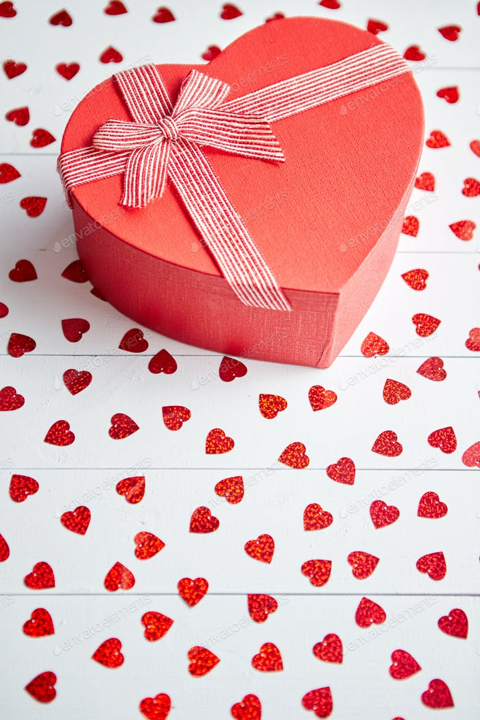Boxed gift placed on heart shaped red sequins on white wooden table