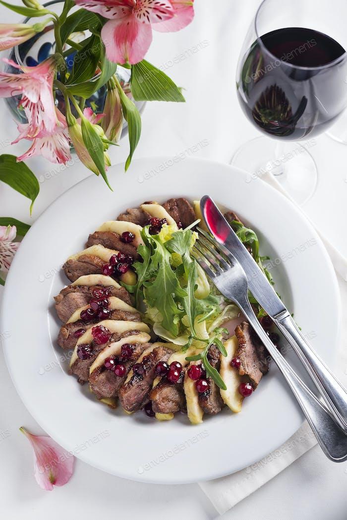 Salat mit Scheiben Entenbrust mit Äpfeln und Salat unter Preiselbeersauce