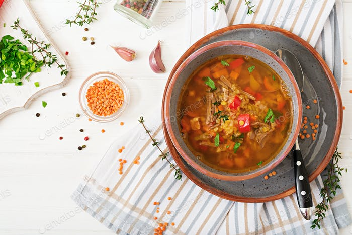 Appetizing soup with red lentils, meat, red paprika and fragrant thyme. Flat lay. Top view