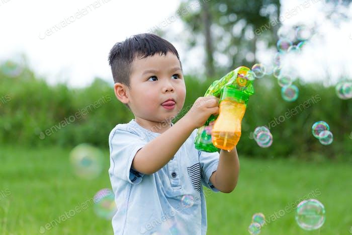 Симпатичный мальчик играть с пузырьковым мылом