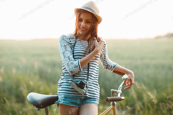 Lovely young woman stands in a field with her bicycle
