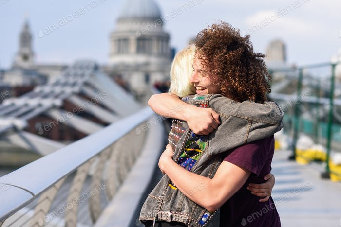 Happy couple hugging by Millennium bridge, River Thames, London