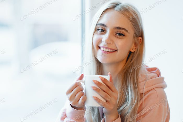 An elf alike, young girl enjoying a cup of coffee or milk while