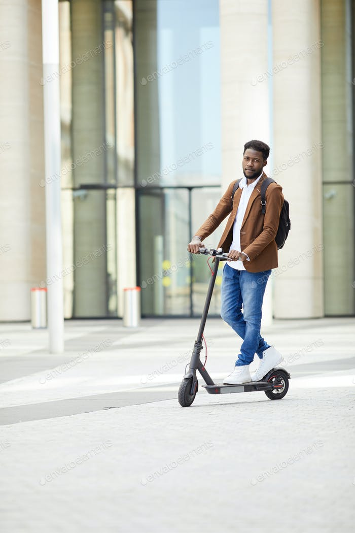 African-American Man Riding Electric Scooter in City