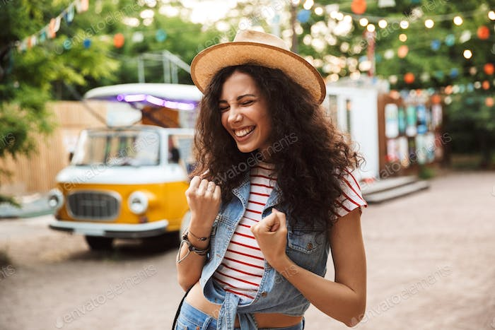 Photo of cheerful happy woman 18-20 with curly brown hair, clenc