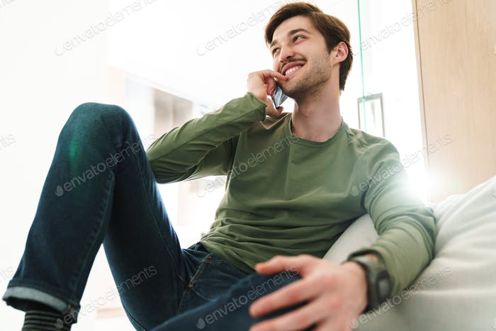 Photo of cheerful young man smiling and talking on smartphone