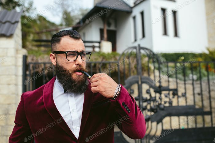 A rich man with a beard smokes cradle