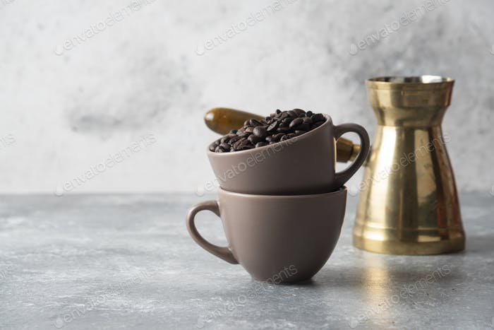 Cup full of coffee beans and coffee maker on marble background