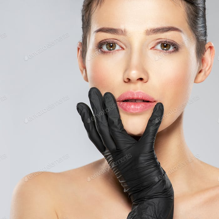 Woman is touching her face before plastic surgery.
