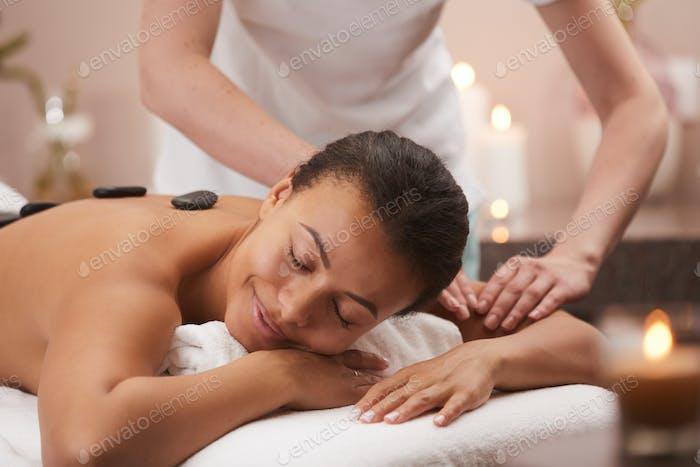 Woman Enjoying Stone Massage in Spa