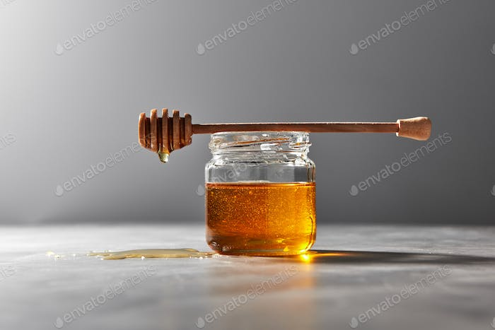 Fragrant natural organic honey dripping from wooden stick into a gray kitchen table. Jewish New Year